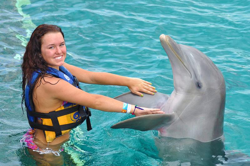 Mujer Joven interactuando con delfín
