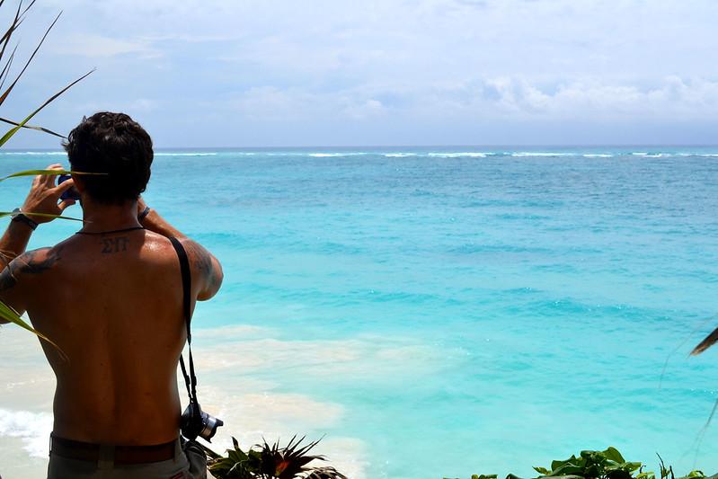 Turista admirando el mar turquesa desde zona arqueológica e Tulum