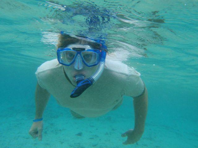 Hombre joven bajo el agua practicando snorkel