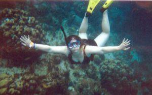 Mujer joven bajo el agua haciendo snorkel