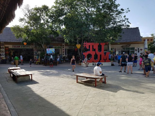 Para dor turistico en el centro de Tulum con letras rojas de #Tulum