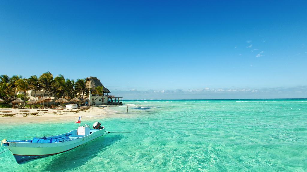 Playa de isla mujeres con aguas cristalinas y una lancha tipica