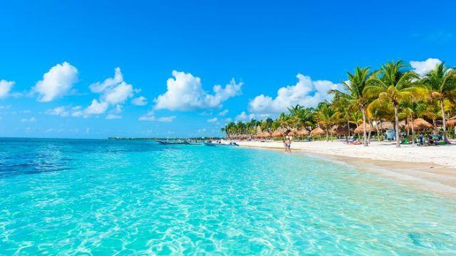 Paisaje de la playa con agua turquesa cristalina con ala rena blanca, palmeras y una pareja de turistas a lo lejos