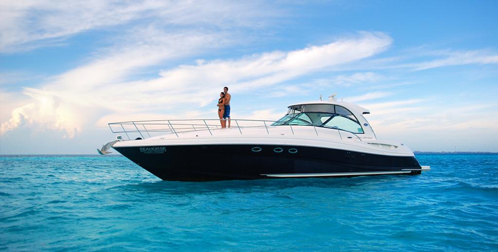 Modenor yate privado en las aguas turquesas de cancún con una pareja joven en la cubierta